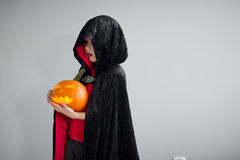 Child is dressed in black -red toga with hood. It is a costume for Halloween. He represents the mysterious wizard. The hood covers the face. Child holds Stock Photography