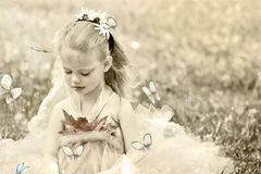 Child Dressed in Fairy Costume. Tiny little woodland fairy whispers sweet stories to the butterflies. Photo based illustration Royalty Free Stock Photo