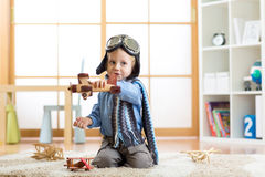 Child dressed like pilot aviator plays with a toy airplanes at home in his room Royalty Free Stock Photos