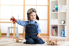 Child dressed like pilot aviator plays with a toy airplanes at home in his room Royalty Free Stock Photography