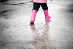 Child dressed in pink clothes jumping in puddles royalty free stock photos