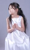 Child dressed in white satin Stock Photo