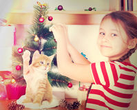Child dresses up Christmas tree. A child dresses up Christmas tree Royalty Free Stock Photos