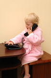 The child in a dressing gown calls by phone Stock Image