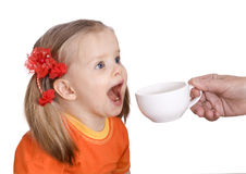 Child drink  water from  white cup. Royalty Free Stock Photography