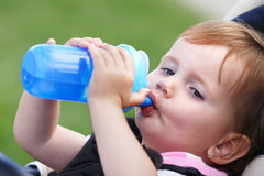 Child drinking. Two years old girl child drinking from blue plastic bobtle Royalty Free Stock Photo