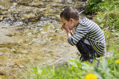 Child drinking clean river water Stock Photo