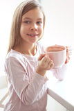 Child drinking cocoa. 7 years old girl drinking hot cocoa from the big pink cup Royalty Free Stock Photo