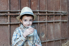 Child drinking a glass of fresh milk. Child with hat is drinking a glass of fresh milk Royalty Free Stock Photography
