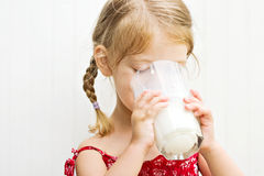Child drinking a glass of milk. Cute little girl drinking a large glass of milk Royalty Free Stock Photos