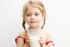 Child drinking a glass of milk. Cute little girl drinking a large glass of milk with a milk mustache Stock Photos