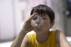Child drinking a glass of pure water. Healthy concept stock images