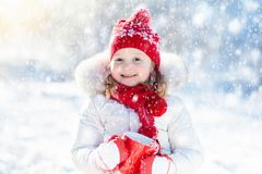 Child drinking hot chocolate in winter park. Kids in snow on Chr Stock Image