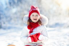 Child drinking hot chocolate in winter park. Kids in snow on Chr Stock Images
