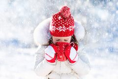 Child drinking hot chocolate in winter park. Kids in snow on Chr. Child drinking hot chocolate with marshmallows in snowy winter park. Kid with cup of warm cocoa Royalty Free Stock Images