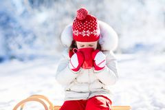 Child drinking hot chocolate in winter park. Kids in snow on Chr Royalty Free Stock Image
