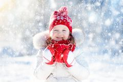 Child drinking hot chocolate in winter park. Kids in snow on Chr Stock Photo