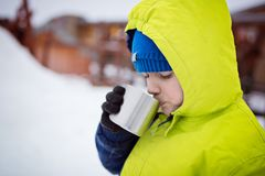 Child drinking hot tea from the metal mug. Stock Images