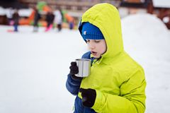 Child drinking hot tea from the metal mug. Royalty Free Stock Photos