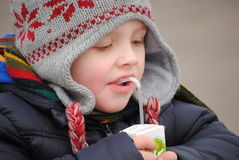 Child drinking juice. Little boy drinking juice in the cold,winter day stock images