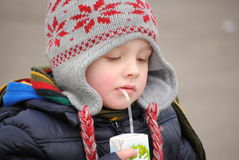 Child drinking juice. Little boy drinking juice in the cold,winter day royalty free stock photos