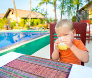 Child drinking juice. Near a swimming pool Stock Image
