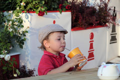 Child drinking juice. The child drinking juice in the outdoor cafe Royalty Free Stock Image
