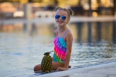 Child drinking juice in swimming pool bar. stock image