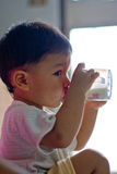Child drinking milk. Profile of cute young child drinking milk Royalty Free Stock Photos