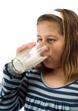 Child Drinking Milk. A young female child drinking a glass of milk, isolated against a white background Stock Image