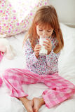 Child drinking milk in bed Stock Image
