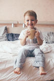 Child drinking milk in the bed Stock Images