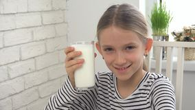 Child Drinking Milk at Breakfast in Kitchen, Girl Tasting Dairy Products stock photography