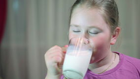 Child drinking milk from glass. Girl with beautiful blond hair. A child 8 years old stock video footage