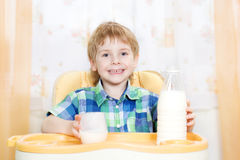 Child drinking milk. Holding glass of milk Royalty Free Stock Photography