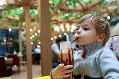 Child drinking milk shake. At table in restaurant Royalty Free Stock Images