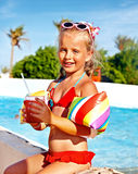 Child drinking  near swimming pool. Stock Photos