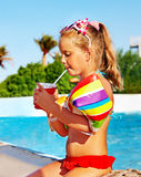 Child drinking  near swimming pool. Stock Image