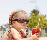 Child drinking orange juice. Royalty Free Stock Images