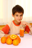 Child drinking orange juice Royalty Free Stock Images