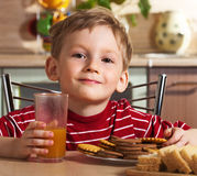 Child drinking orange juice Royalty Free Stock Image