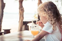 Child drinking orange juice beach summer holidays vacation childhood traveling lifestyle. Child drinking orange juice beach summer holidays vacation concept for royalty free stock images
