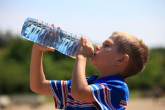 Child drinking pure water in nature. From a bottle Royalty Free Stock Image