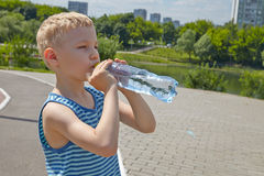Child drinking pure water in a park Stock Photography