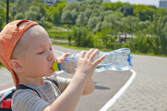 Child drinking pure water in a park Royalty Free Stock Images