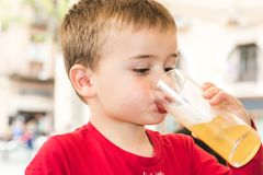 Child drinking a soda in a glass stock photos