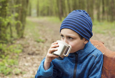 Child drinking tea in nature park Royalty Free Stock Photography