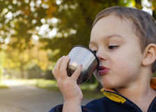 Child drinking tea in park Stock Photo