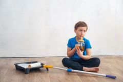 Child is drinking tea during the repair of the wall. finishing work in the premises of the artist paints the walls. repair of royalty free stock photo
