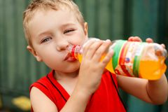 Child drinking unhealthy soda. Kid consuming sugar beverage. Child drinking unhealthy sweet bottled soda. Kid drinking sugar beverage. Poverty and health concept stock photography